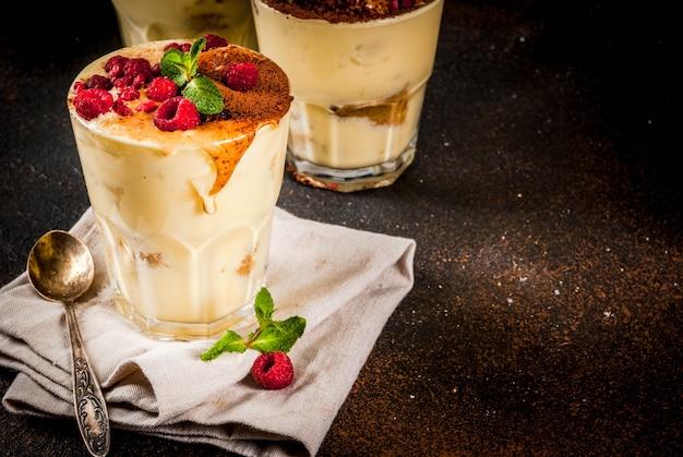 Bicchiere a tre porzioni con tiramisù dolce italiano, con menta e lamponi