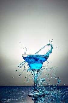 Bicchiere con champagne blu o cocktail. levitazione
