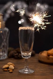 Bicchiere con champagne e fuochi d'artificio