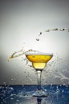 Bicchiere con champagne giallo o cocktail.
