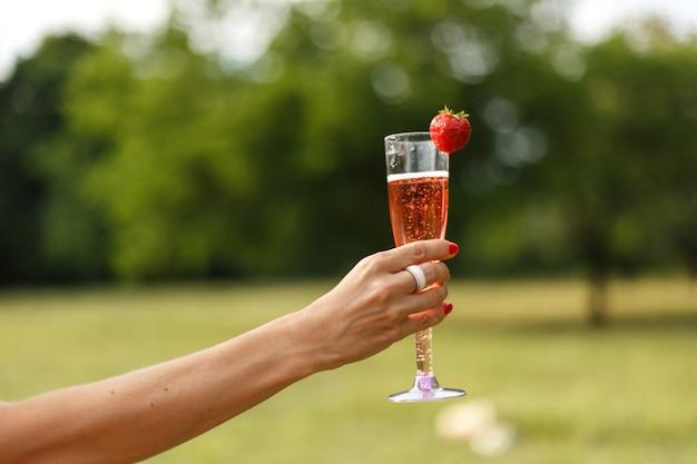 Bicchiere con champagne in mano.