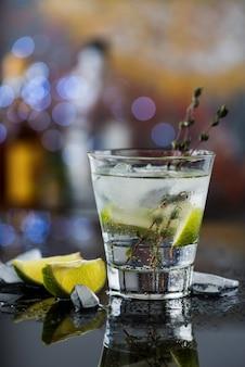 Bicchiere con cocktail con lime, timo e ghiaccio