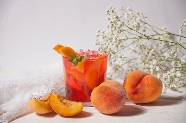 Bicchiere con tè o cocktail freddo dolce alla pesca fatto in casa, limonata alla menta. bevanda fredda rinfrescante. festa estiva.