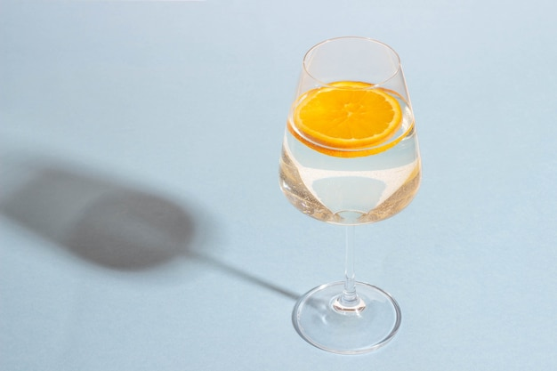 Bicchiere con una bevanda estiva e una fetta d'arancia su uno sfondo blu brillante con ombre dure.