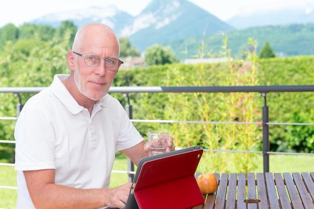 Bicchiere d'acqua bevente dell'uomo maturo sul terrazzo del giardino