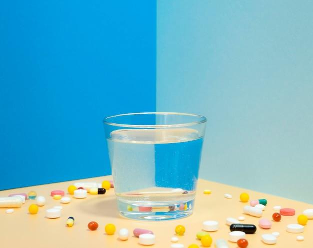 Bicchiere d'acqua con assortimento di pillole che lo circonda