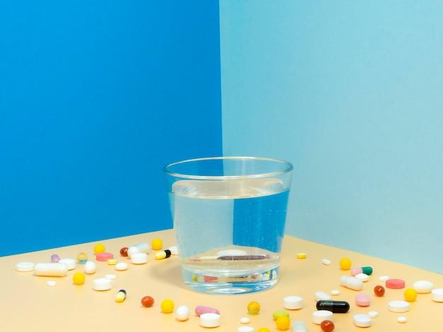 Bicchiere d'acqua con le pillole che lo circondano e lo spazio della copia