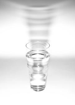 Bicchiere d'acqua con ombra su sfondo bianco