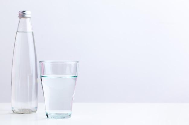 Bicchiere d'acqua con una bottiglia sul tavolo