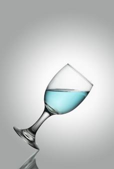 Bicchiere d'acqua di champl di tlted su fondo bianco
