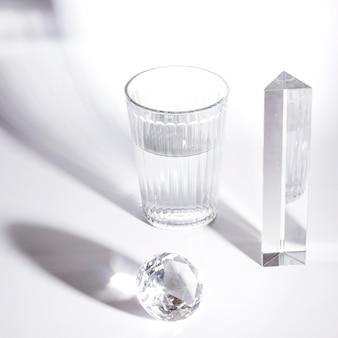 Bicchiere d'acqua; diamante di cristallo e prisma con forti ombre su sfondo bianco