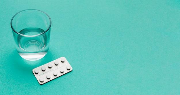 Bicchiere d'acqua e pillole con copia-spazio