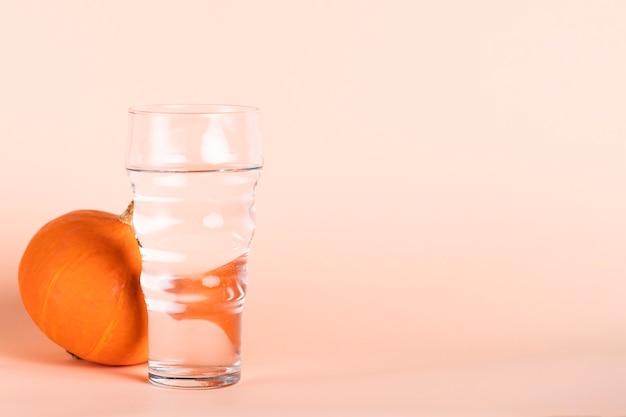 Bicchiere d'acqua e zucca con copia-spazio