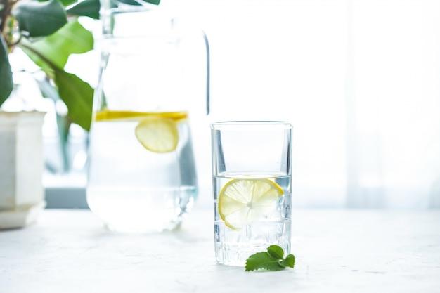 Bicchiere d'acqua, ghiaccio, menta e limone su una tavola bianca