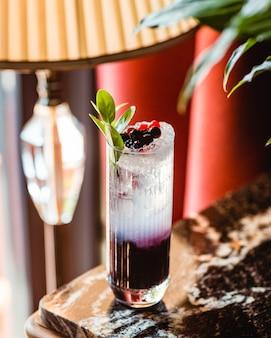 Bicchiere d'acqua mezzo viola mezzo trasparente guarnito con bacche