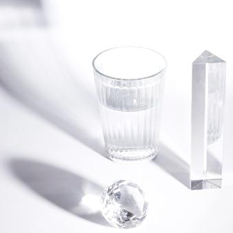 Bicchiere d'acqua; prisma; diamante scintillante su sfondo bianco