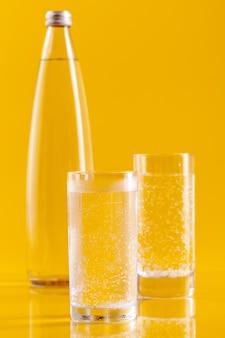 Bicchiere d'acqua su fondo giallo. uno stile di vita sano