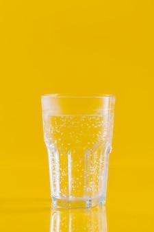 Bicchiere d'acqua su fondo giallo