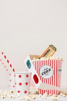 Bicchiere da asporto con paglia; occhiali 3d; biglietti del cinema e scatola di popcorn su sfondo bianco