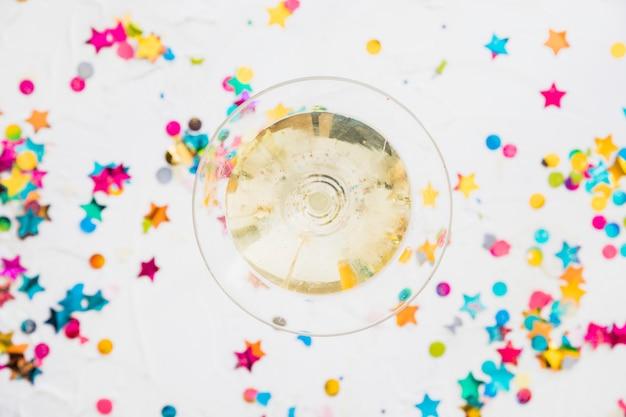 Bicchiere da champagne con lustrini a stella sul tavolo
