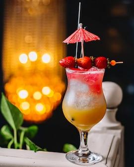 Bicchiere da cocktail a tre strati guarnito con fragola e ombrello da cocktail