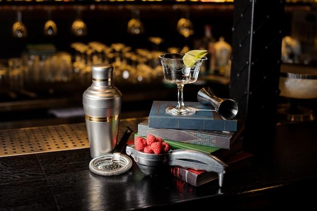 Bicchiere da cocktail con fetta di lime e utensili da bar disposti tra i libri