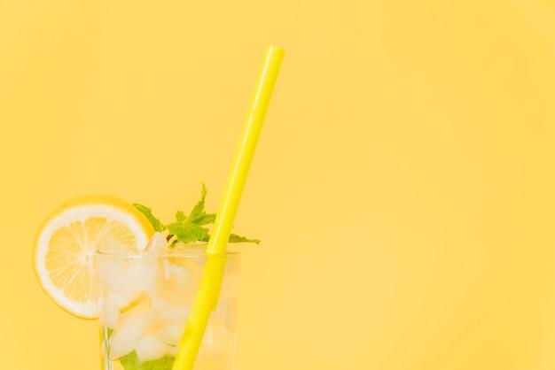 Bicchiere da cocktail con paglia e limone su sfondo giallo