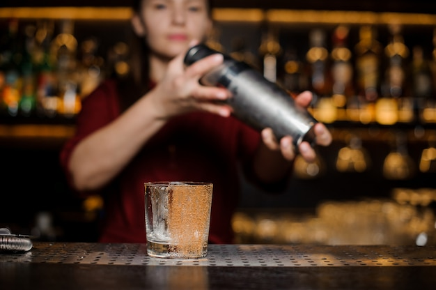 Bicchiere da cocktail decorato con cannella sullo sfondo sfocato del barista