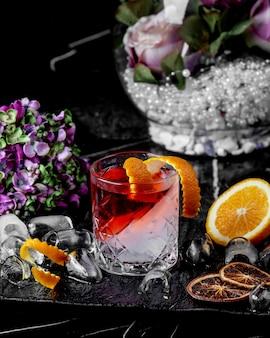 Bicchiere da cocktail rosso e bianco con scorza d'arancia