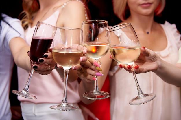 Bicchiere da vino di vino freddo in mani femminili.