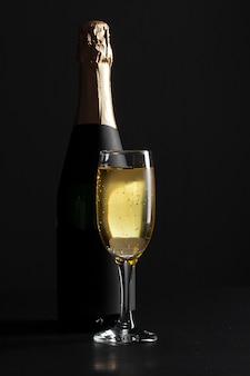 Bicchiere da vino e bottiglia di champagne su fondo nero
