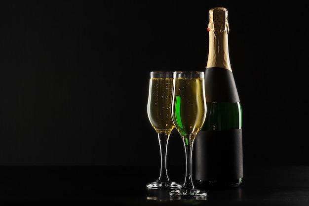 Bicchiere da vino e bottiglia di champagne sul nero