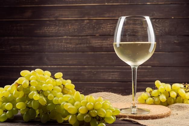 Bicchiere da vino e grappolo d'uva sul tavolo di legno