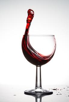 Bicchiere da vino puro con un'ondata di vino rosso brillante