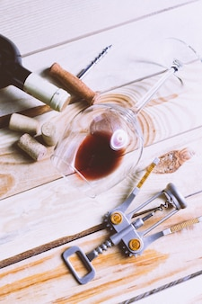Bicchiere da vino, sughero e cavatappi sul tavolo di legno