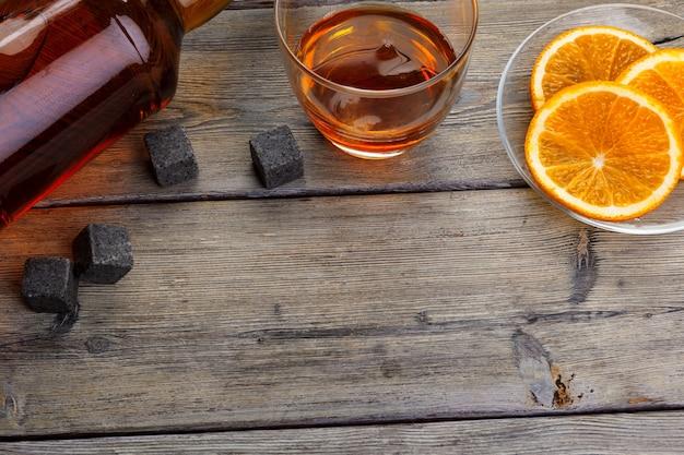 Bicchiere da whisky con frutta arancione tagliato su legno scuro