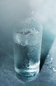 Bicchiere di acqua chiara fredda su uno sfondo blu con gocce che cadono in un bicchiere.