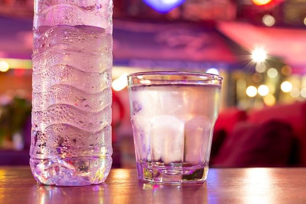 Bicchiere di acqua fredda con bottiglia in luci pazzesche estremamente colorate.