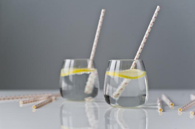 Bicchiere di acqua limpida con limone e paglia.