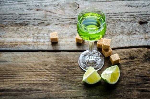 Bicchiere di assenzio con cubetti di lime e zucchero