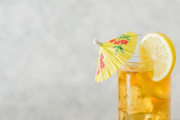 Bicchiere di bevanda al limone con ombrello e copia spazio