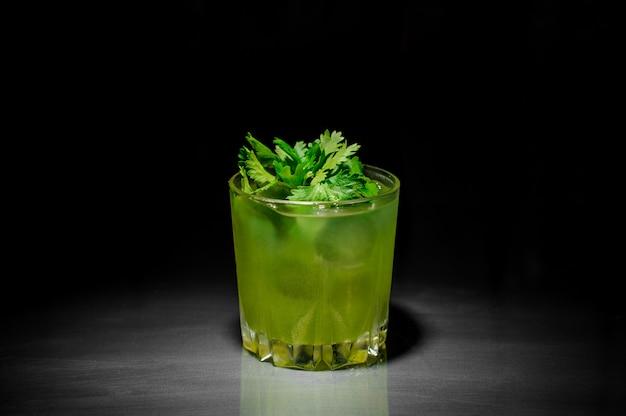 Bicchiere di bevanda alcolica fresca con ghiaccio decorato con foglie di prezzemolo