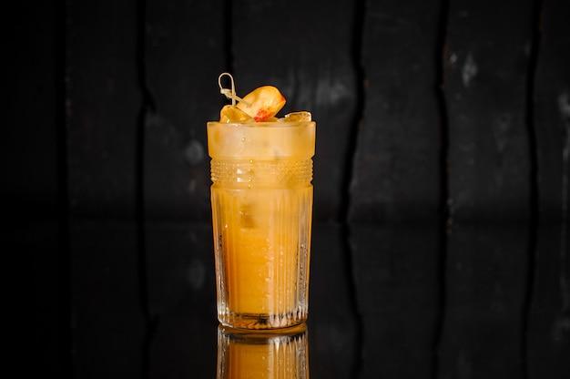 Bicchiere di bevanda alcolica fresca con ghiaccio decorato con pezzi di pesca