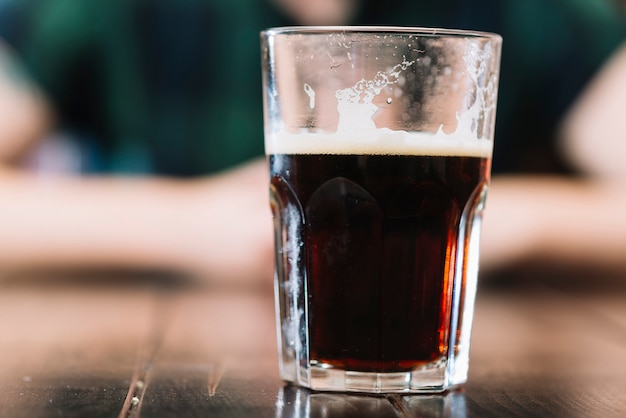 Bicchiere di bevanda alcolica sul tavolo di legno