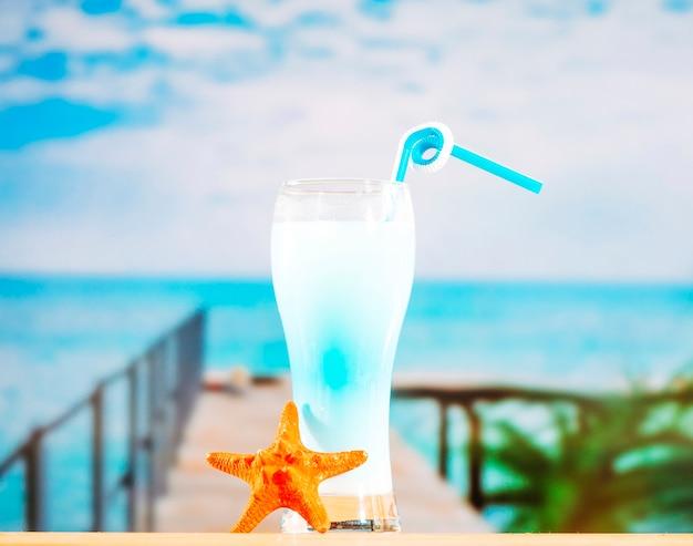 Bicchiere di bevanda blu congelato con paglia e stelle marine