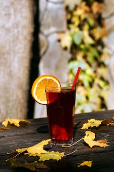 Bicchiere di bevanda calda e foglie di autunno sul tavolo di legno.
