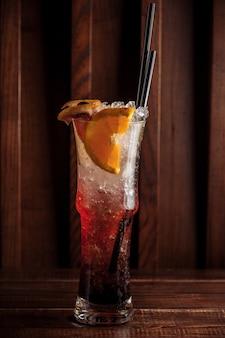 Bicchiere di bevanda di frutta con fette di ghiaccio e arancia