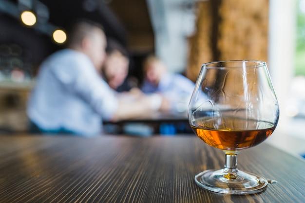 Bicchiere di bevande dorate sulla superficie in legno al ristorante