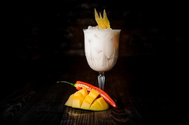 Bicchiere di bianco cocktail alcolici con ghiaccio e fetta di frutta esotica