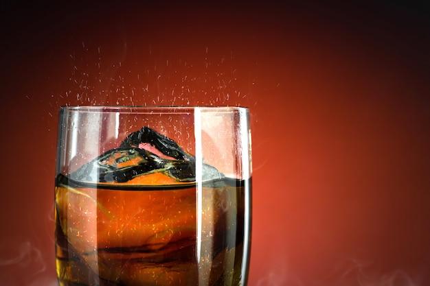Bicchiere di bibita con ghiaccio spruzzata su sfondo fumo freddo. bicchiere di coca con rinfresco estivo.